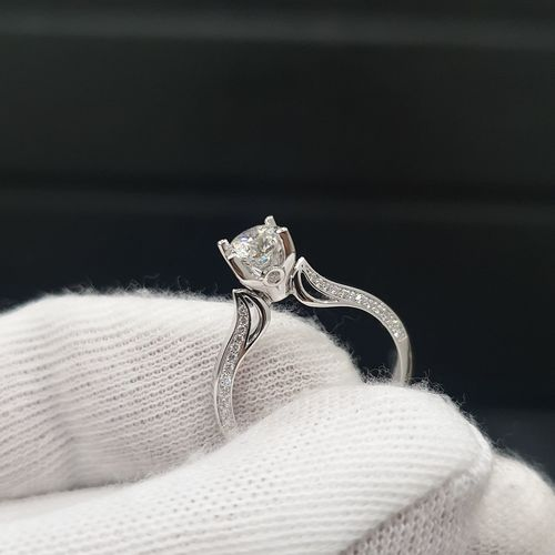 Close-up of cropped hand holding ring against black background