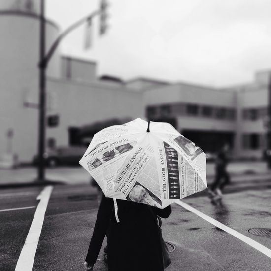 Rear view of person on street holding newspaper print umbrella during rains