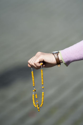 Cropped Image Of Woman Hand Holding Rosary Beads