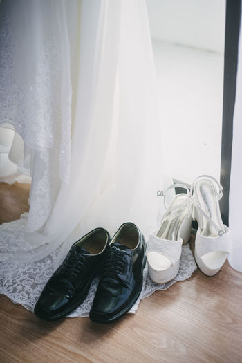 Elegant bride's and groom's shoes on the wooden floor. Groom Wedding Shoes Apparel Bride Bridegroom Clothes Clothing Clothing Store Fashion Flooring Footware Garments Indoors  Low Section Marriage  Outfit Pair Personal Accessory Shoe Shoes Wear Wedding Ceremony Wedding Day Wedding Dress White Color