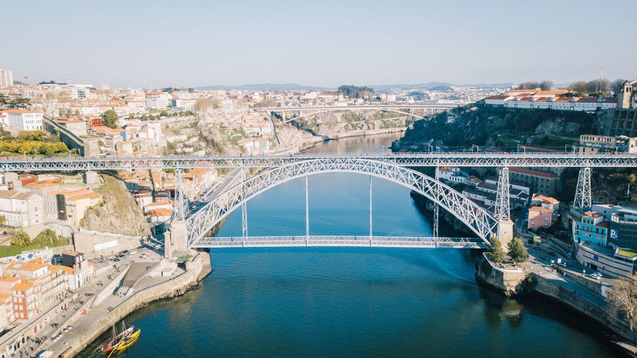 Aerial view of arch bridge over river in city
