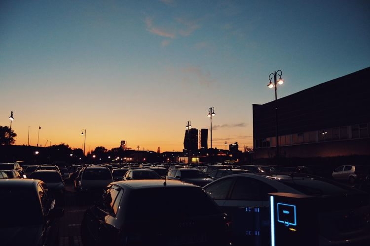 Cars in city against sky during sunset