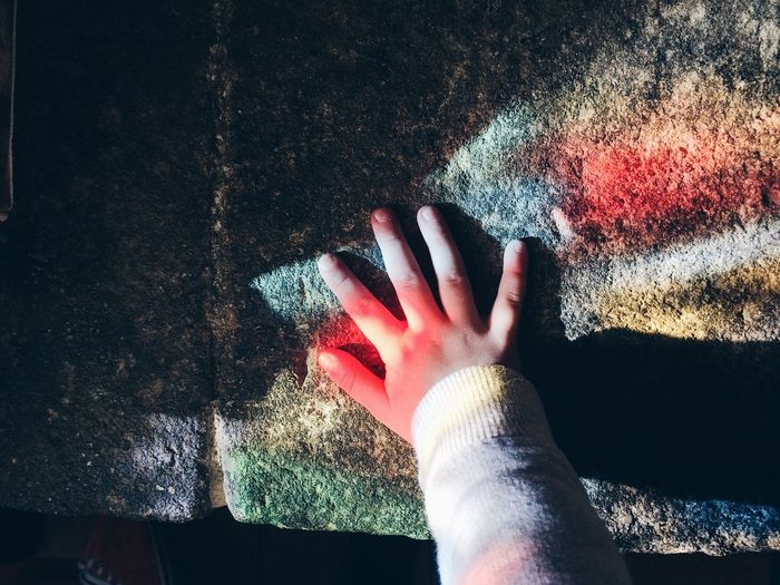 Cropped hand of girl touching weathered wall