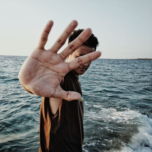 Portrait of young man showing stop gesture against sea