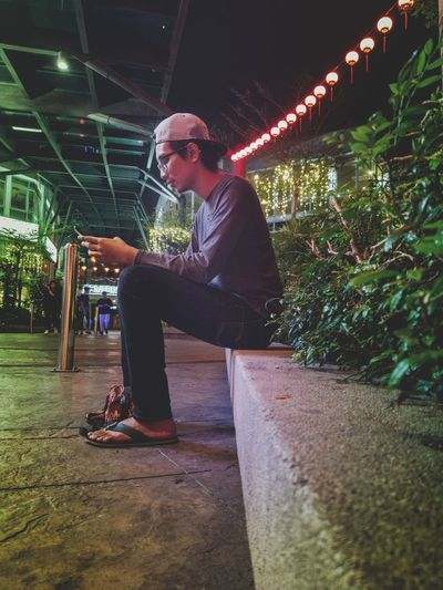 Side view of young man sitting on illuminated plants at night
