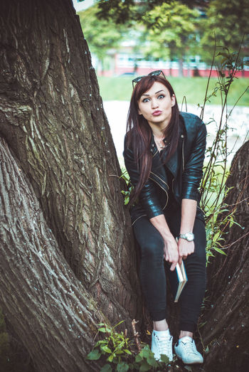 Full length portrait of beautiful woman sitting on tree at park