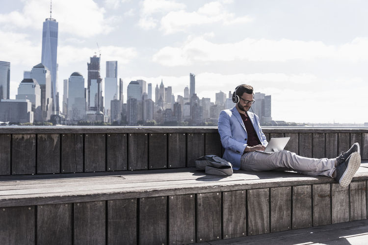 Man sitting on mobile phone against cityscape