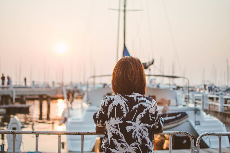 Rear view of woman standing at harbor against clear sky