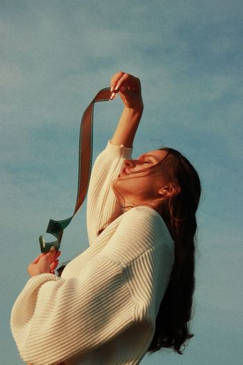 Midsection of woman holding film roll against sky