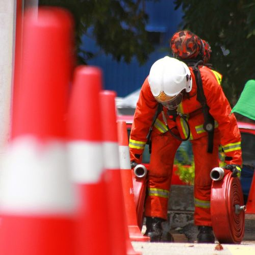 Firefighter With Pipes Standing By Traffic Cones