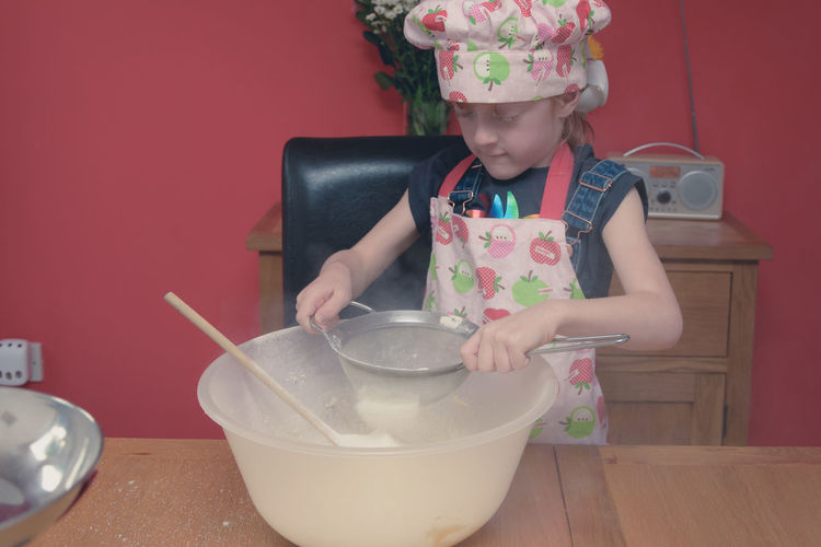 Girl wearing apron straining flour in container on table at home