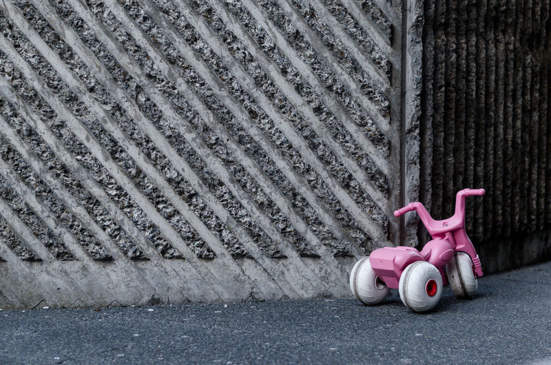 Tricycle On Street By Wall