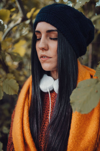 Close-up of young woman standing in forest during winter