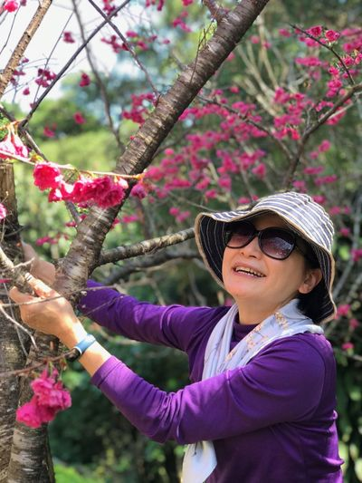 Portrait of woman with pink flowers against trees