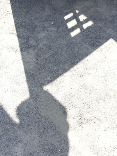 High angle view of shadow on road on sunny day