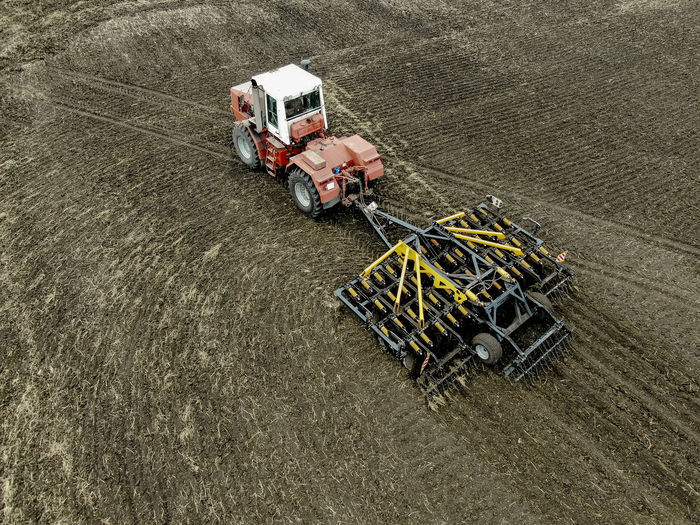 Aerial view of a modern tractor plowing dry field, preparing land for sowing Aerial Agriculture Field Tractor Farm Ground Soil Countryside Combine Machinery Motion Working Plowing Agricultural Machinery Rural Scene Landscape Transportation High Angle View Mode Of Transportation Outdoors Land Vehicle Industry