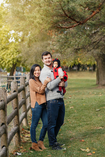 Happy halloween. chinese mother and caucasian father dad with baby girl in ladybug halloween costume