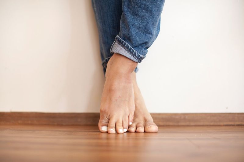 Low section of woman wearing shoes at home