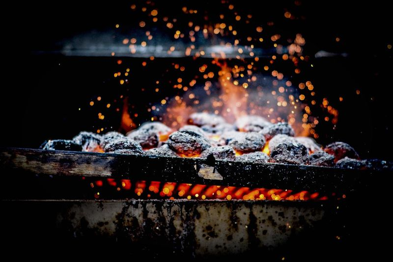Close-up of burning coal on metal grill