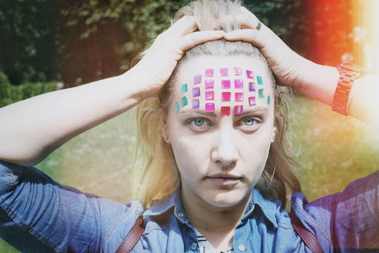 Close-up portrait of mid adult woman with colorful stickers on forehead