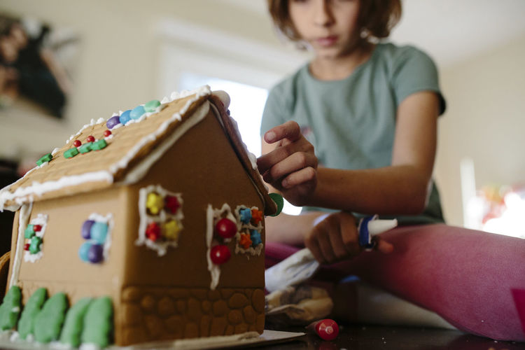 Rear view of girl holding christmas at home
