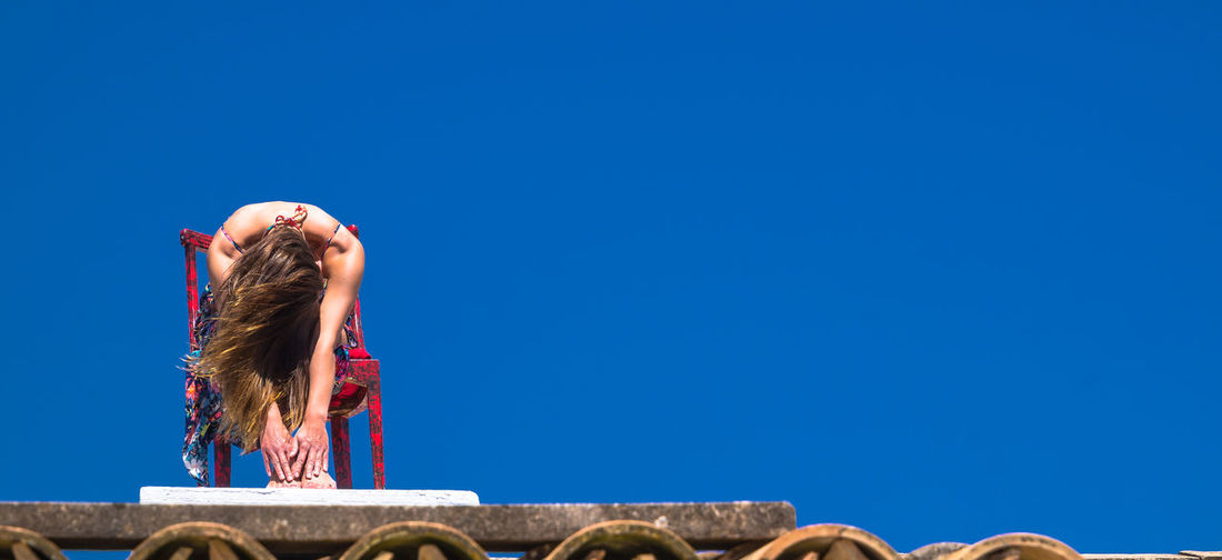 Low angle view of woman sitting on chair at building terrace against clear blue sky