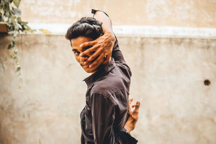 Portrait of young man covering face while standing against wall outdoors