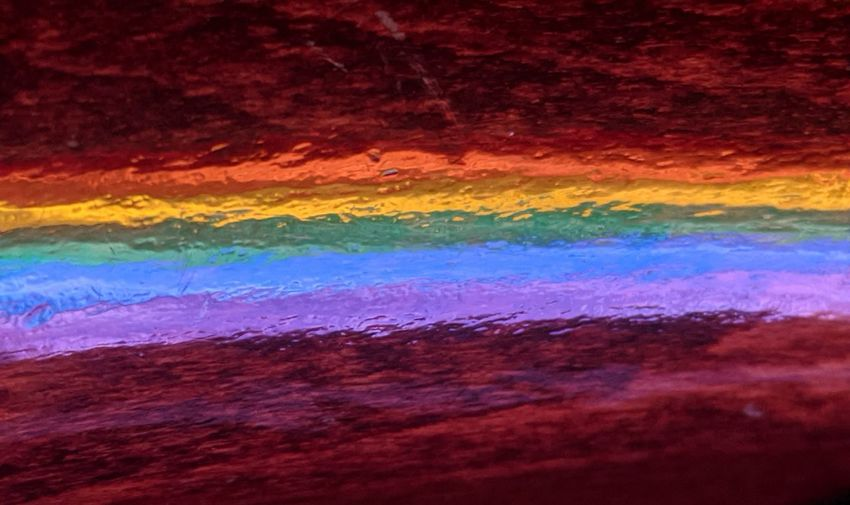Full frame shot of multi colored water on rock against sky at night