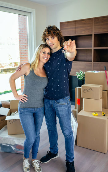 Moving couple showing the keys to their new home Box Cardboard Box Couple Family Happy Man Moving New Unpacking Woman Apartment Cardboard Caucasian Enjoy Female House Key Lifestyles Male Mortgage Packed Real People Relocation Smiling Vertical