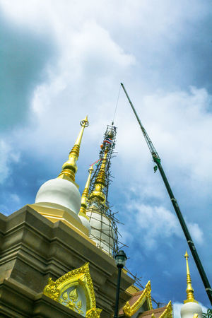 Last construction of pagoda is ceremony of lift the tiered(cap) to the top Architecture; Art; Background; Beautiful; Buddha; Building; Cap; Ceremony; Construction; Crane; Culture; Day Gold; Great; Holy; Landmark; Monk; Outdoors Pagoda; Religion; Sky Temple; Tiered; Top; Traditional;