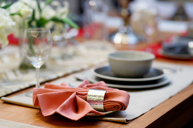 A close up shot of a restaurant table set up with tableware and wine glass. Concept of dining, hospitality and catering. Table Food And Drink Glass Plate Drink Food No People Wineglass Setting Refreshment Household Equipment Place Setting Selective Focus Focus On Foreground Indoors  Still Life Wood - Material Freshness Flower Celebration Crockery Luxury Wine Glass Tableware Reserved Event Luxurious Banquet Table Cutlery Indoors  Nobody Napkin Hospitality Catering Dining