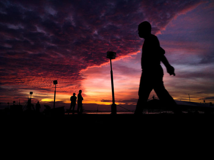 Silhouette people standing against dramatic sky during sunset
