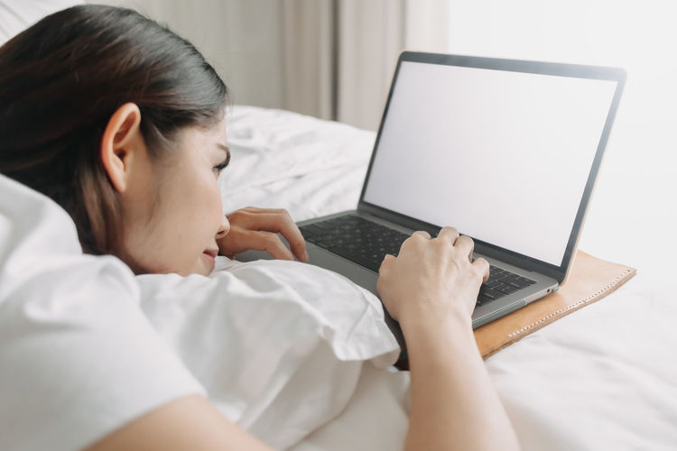 Midsection of woman using mobile phone on bed