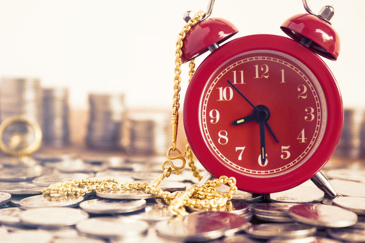 Close-Up Of Alarm Clock On Coins With Gold Chain At Table