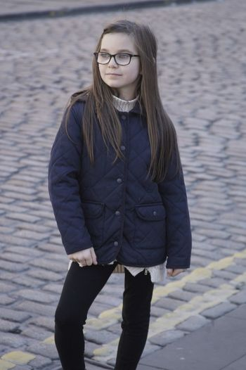 Girl wearing eyeglasses and jacket standing on cobbled street