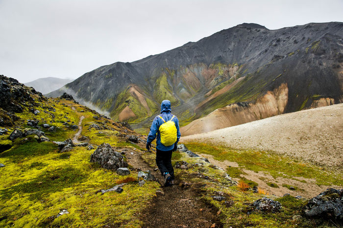 Cloudy Iceland Activity Adventure Backpack Beauty In Nature Day Full Length Hiking Landmanalaugar Leisure Activity Lifestyles Men Mountain Mountain Range Nature Non-urban Scene One Person Outdoors Real People Rear View Scenics - Nature Tarvel Tarvel Destination Tranquil Scene