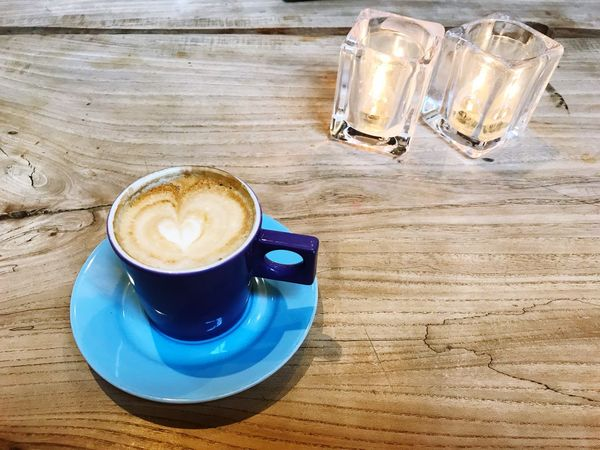 Colorful cup with cappucino on a wooden table with two candles Candleholder Glass Candles Copy Space Table Blue Latte Art Drink Table Refreshment Food And Drink Coffee Cup Coffee - Drink High Angle View No People Saucer Indoors  Wood - Material Frothy Drink Close-up Cappuccino Freshness Froth Art Day