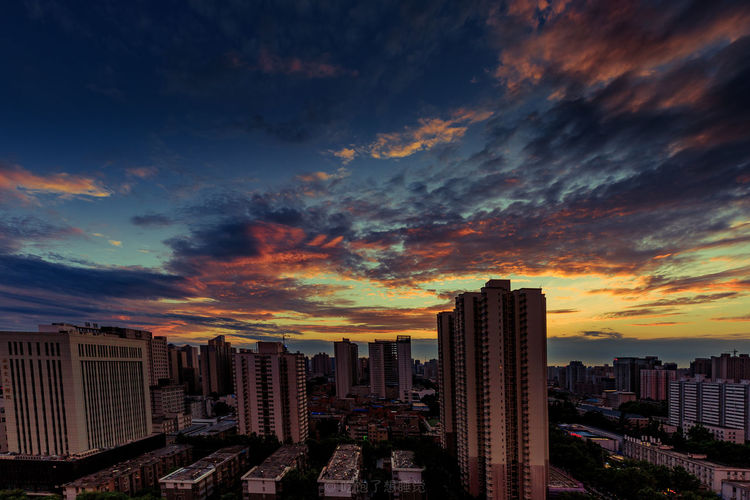 Modern buildings against dramatic sky during sunset