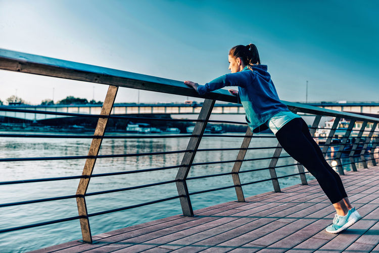 Young Woman Exercising On Promenade By River Against Clear Sky During Sunset