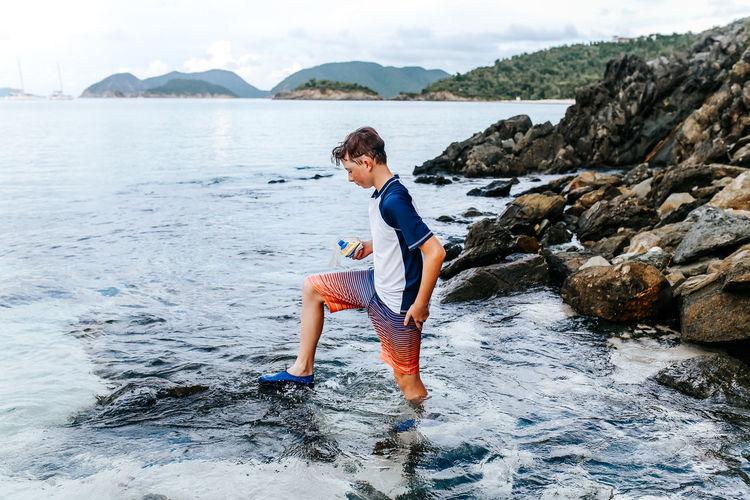 Full length of boy on rock at beach