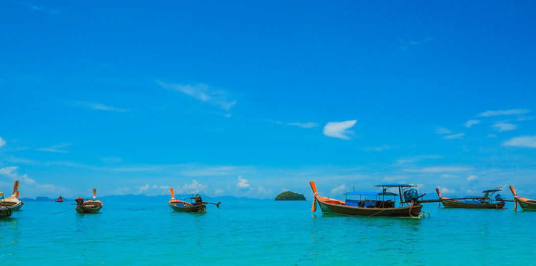 Fishing boats in sea against blue sky