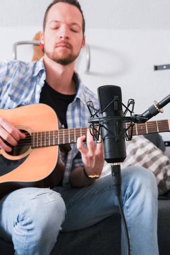 Young man sitting on a couch playing and recording his acoustic guitar lyricaly Music Musical Instrument Sitting Playing Guitar Young Adult One Person Musician Guitarist Guitar Player Playing Guitar Young Men Musical Equipment Acoustic Guitar Fingerpicking Feelings Making Music Love Analogue Sound