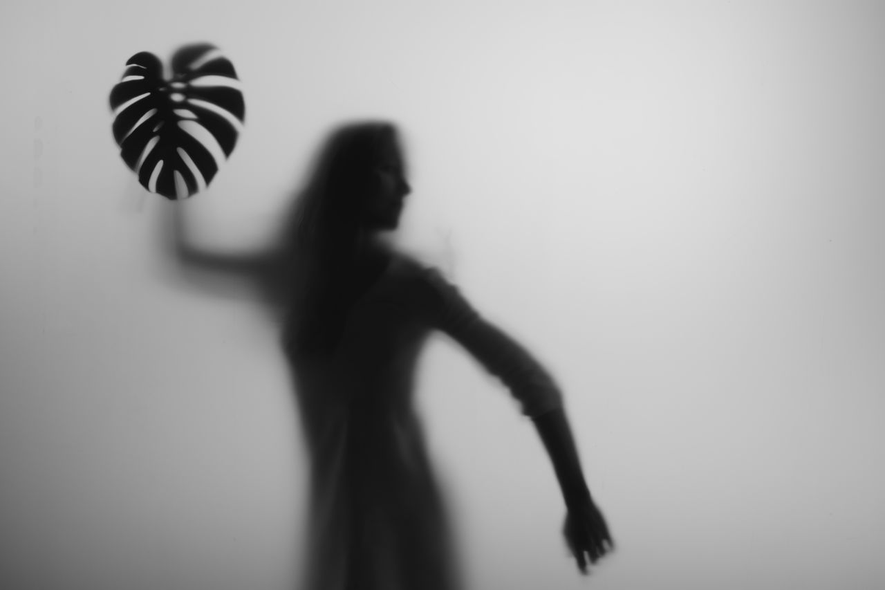 SILHOUETTE OF WOMAN STANDING AGAINST WALL