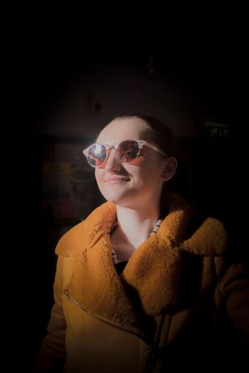 Smiling young woman wearing sunglasses and coat at home