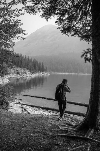 enjoying the outdoor elements Blackandwhite Monochrome Water Tree Lake Full Length Adventure Sky Hiker Woods Rocky Mountains Shore Foggy Scenics Hiking Mountain Mountain Range Pine Woodland