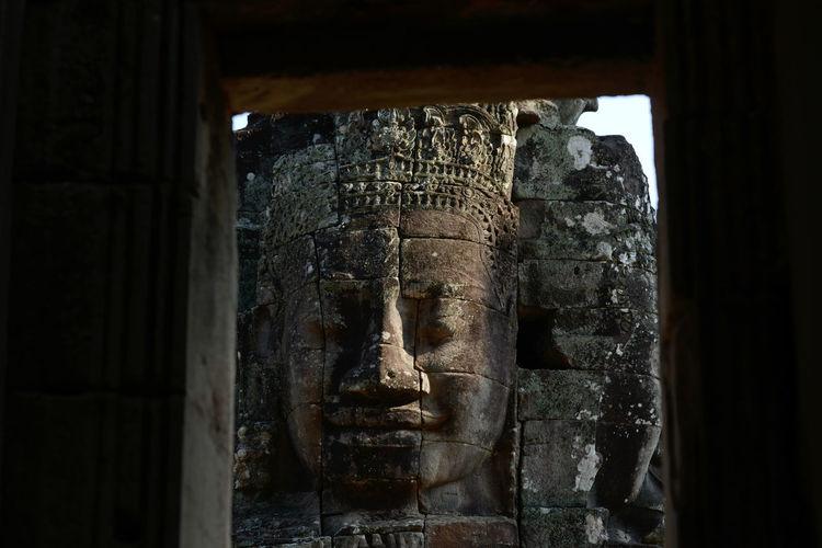 Buddha carving on bayon temple seen through window