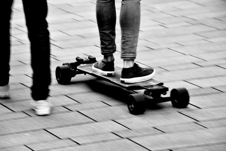 Low section of man walking with friend skateboarding on street