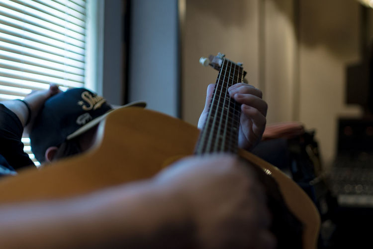 Midsection of man playing guitar while sitting at home