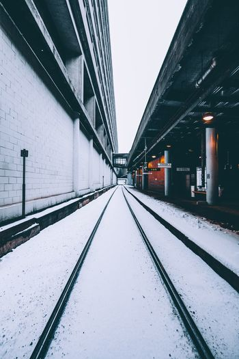 Railroad tracks against sky during winter