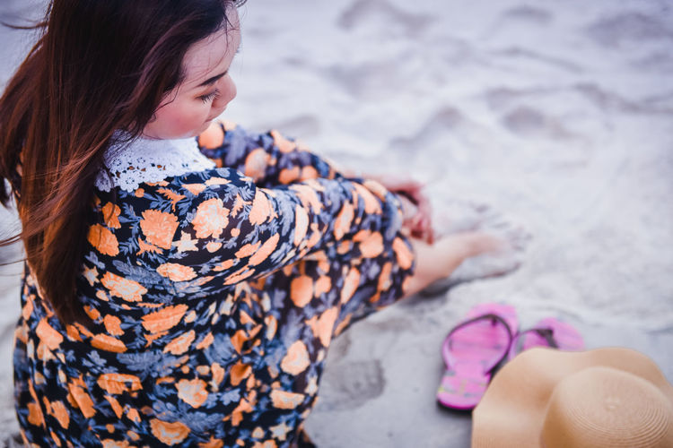 High angle view of woman sitting on sand at beach